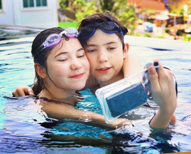 Kinder mit Unterwasserkamera im Swimmingpool stockfotografie