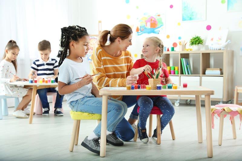 Kinder mit weiblichem Lehrer an malender Lektion stockbild