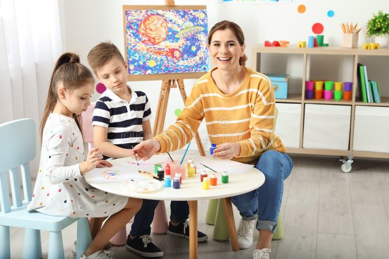 Kinder mit weiblichem Lehrer an malender Lektion stockfotografie