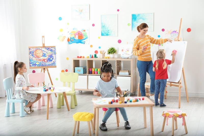 Kinder mit weiblichem Lehrer an malender Lektion lizenzfreies stockfoto