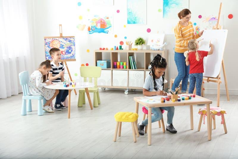 Kinder mit weiblichem Lehrer an malender Lektion lizenzfreie stockbilder
