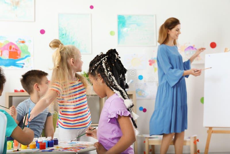 Kinder mit weiblichem Lehrer an malender Lektion stockfotos