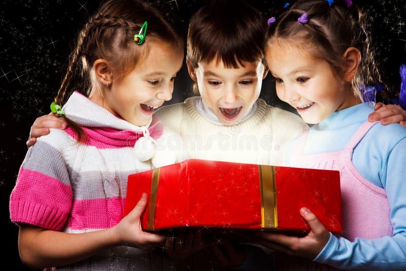 Kinder mit Weihnachtsgeschenk lizenzfreies stockbild