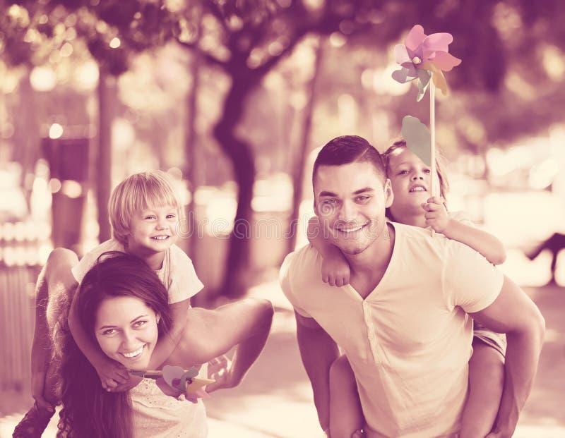 Kinder mit Windmühlen auf parent's Armen lizenzfreie stockbilder