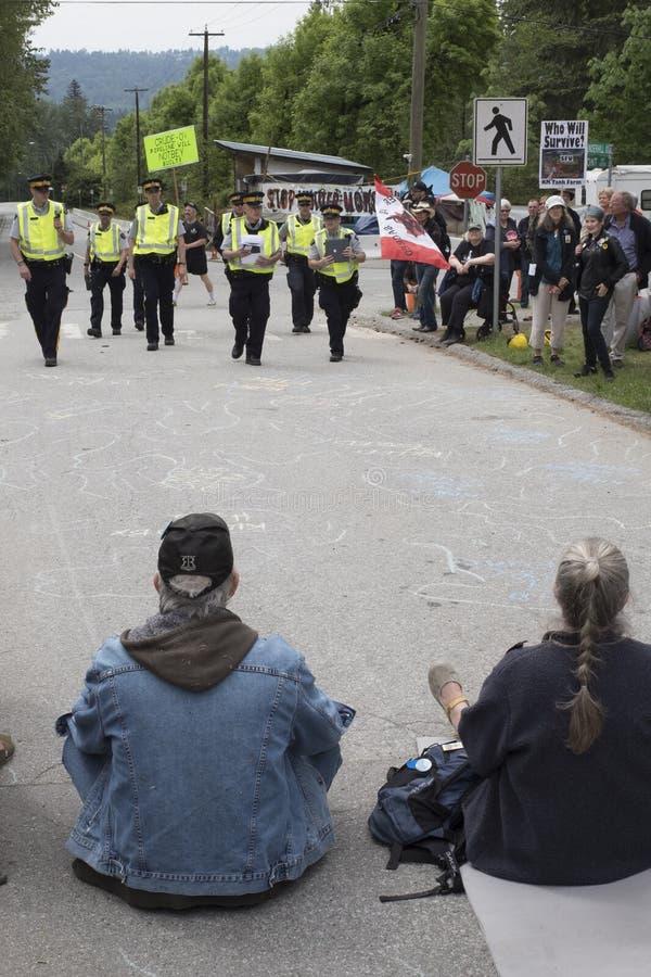 Kinder Morgan-de protesteerders kijken aangezien de politie hen komt arresteren royalty-vrije stock afbeeldingen