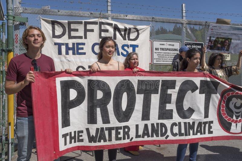Kinder Morgan protesters block the Kinder Morgan tank farm gate in Burnaby, BC. Kinder Morgan protesters hold a protest sign while they block the main gate to royalty free stock photos