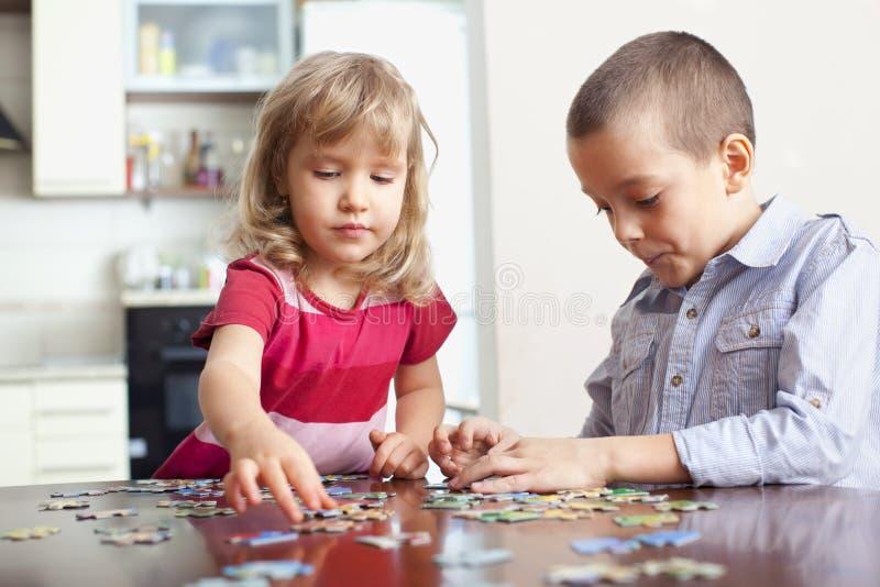 Kinder, Puzzlespiele spielend lizenzfreie stockfotos