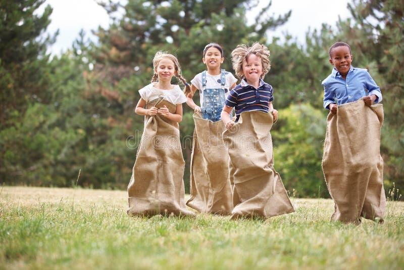 Kinder am Sackrennen stockfotografie