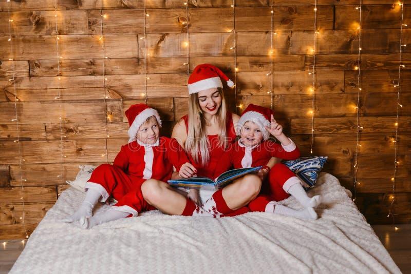 Kinder in Sankt-Kostümen lasen mit Mutterbuch stockfotografie