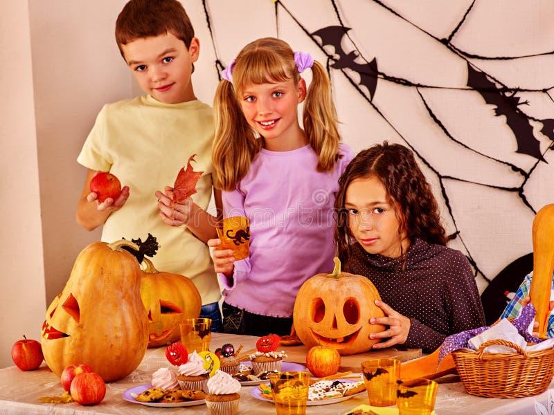 Kinder schauen vorwärts zu Halloween Sie machen geschnitzten Kürbis stockfotografie