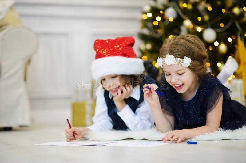 Kinder schreiben Santa Claus Briefe stockbilder