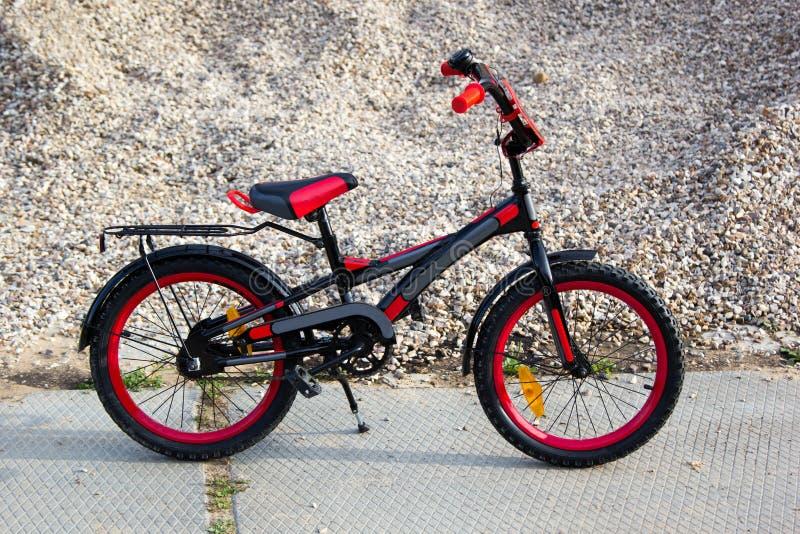 Kinder schwarz und rotes Fahrrad auf Kieshintergrund lizenzfreie stockfotografie
