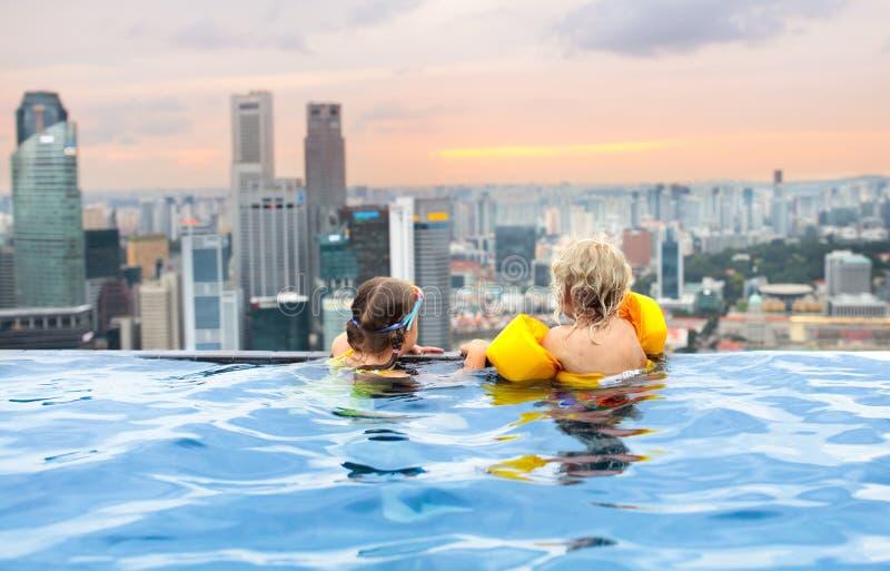 Kinder schwimmen im Singapur-Dachspitzen-Swimmingpool stockbilder
