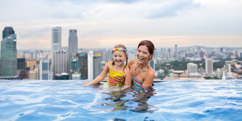 Kinder schwimmen im Singapur-Dachspitzen-Swimmingpool stockfotos