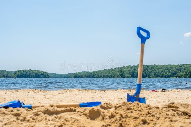 Kinder setzen blaue Schaufel der Werkzeuge auf See des blauen Wassers auf den Strand stockbilder