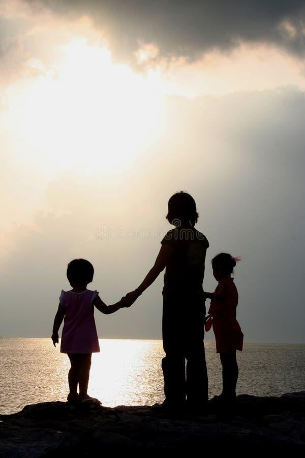 Kinder silhouettiert am Sonnenuntergang lizenzfreies stockfoto