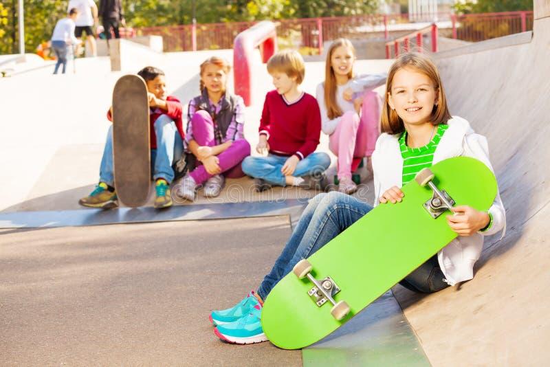 Kinder sitzen hinten und Mädchen in der Front mit Skateboard stockbilder