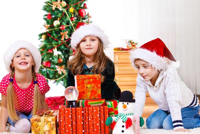 Kinder sitzen neben Weihnachtsgeschenken lizenzfreie stockbilder