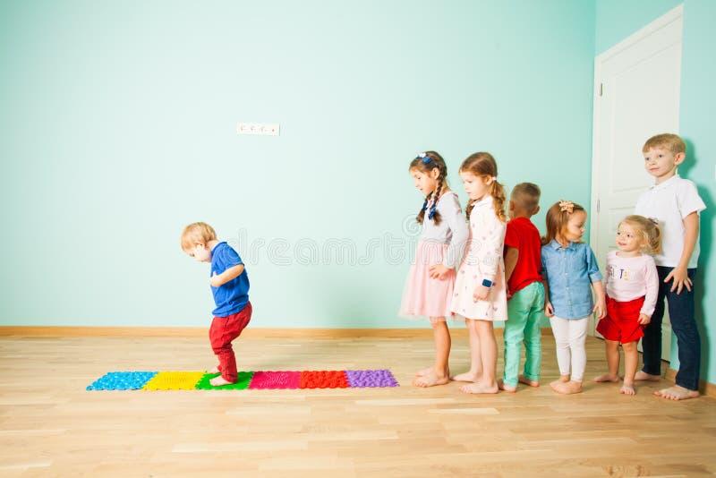 Kinder stehen barfuß in Folge zwischen Massagematten lizenzfreies stockbild