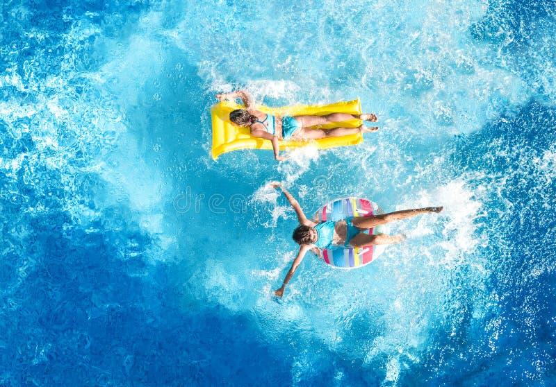 Kinder in Swimmingpoolluftbrummenansicht fom oben, glückliche Kinder schwimmen auf aufblasbarem Ringdonut und -matratze lizenzfreie stockfotos