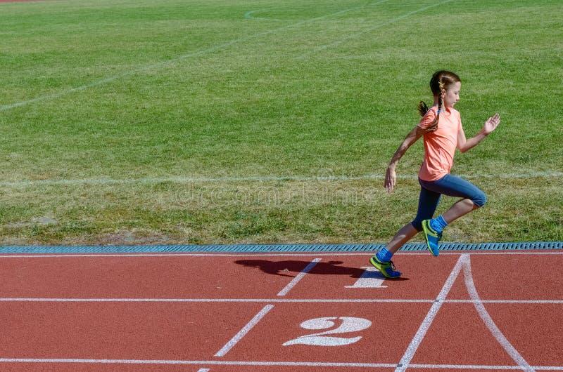 Kinder tragen, das Kind zur Schau, das auf Stadionsbahn laufen, Training und Eignung stockfotografie