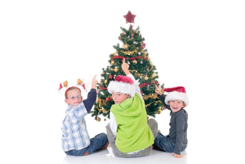 Kinder um Weihnachten drei lizenzfreie stockfotos