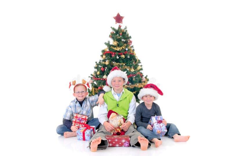 Kinder um Weihnachten drei lizenzfreie stockfotografie