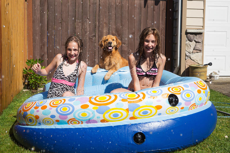Kinder und ein Hund, der in einem Pool spielt lizenzfreies stockfoto
