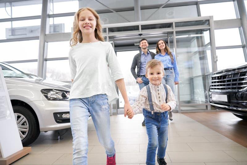 Kinder und Eltern, die in Automittelausstellungsraum gehen lizenzfreie stockfotos
