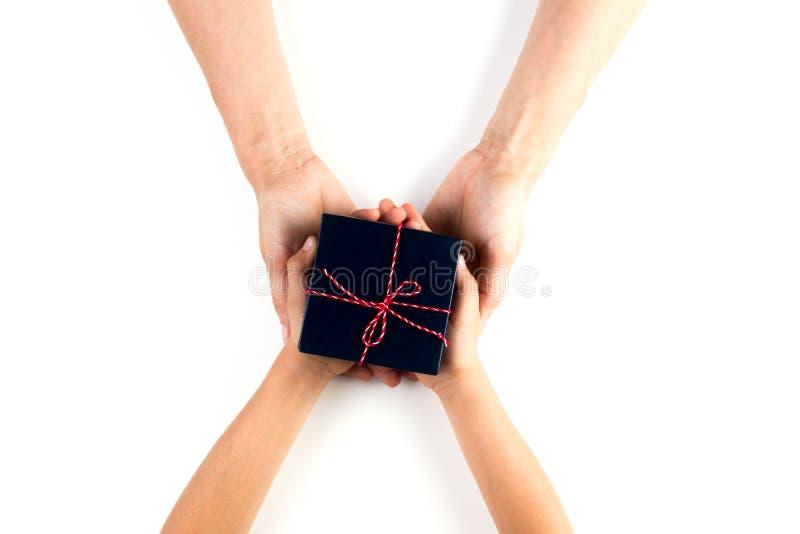 Kinder- und Erwachsenhände, die ein Geschenk geben und empfangen stockfoto