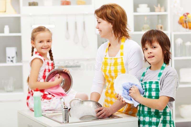 Kinder und ihre waschenden Teller der Mutter stockbilder