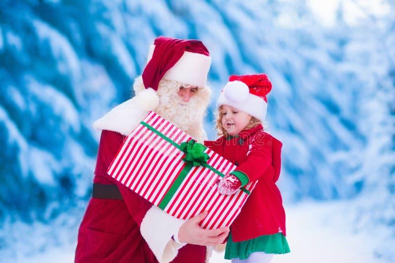 Kinder und Sankt mit Weihnachtsgeschenken stockfotos