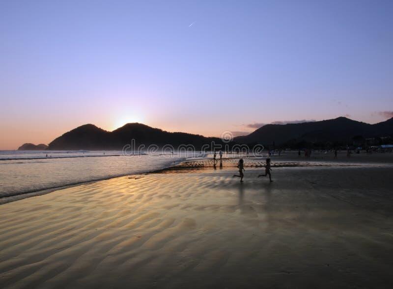 Kinder und Sonnenuntergang-Reflexion an einem tropischen Strand stockbild
