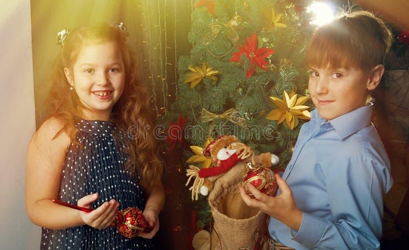 Kinder verzieren Weihnachtsbaum stockfotografie