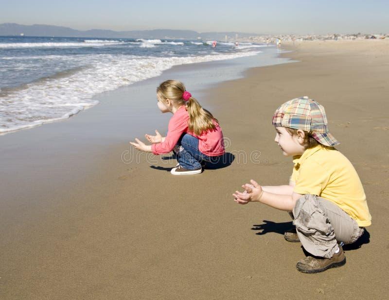 Kinder warten eine Welle stockfotos