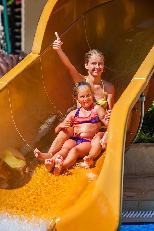 Kinder am Wasserpark schieben unten und zeigen sich Daumen lizenzfreie stockfotografie