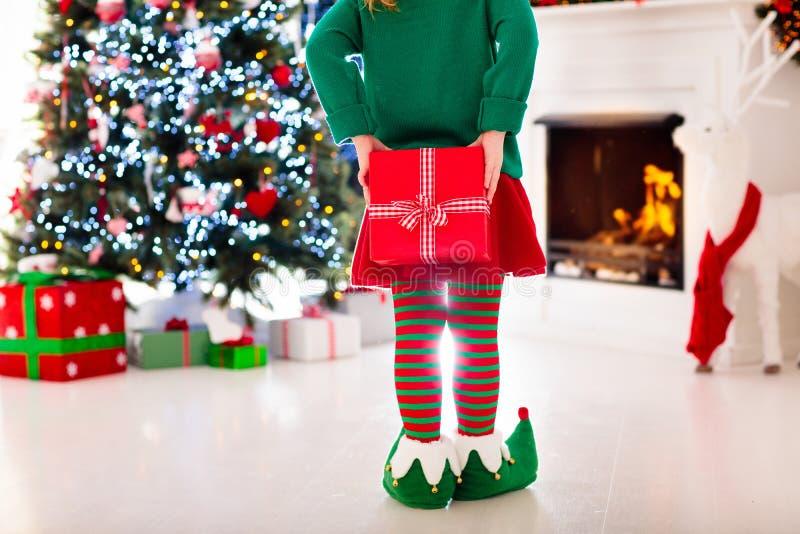 Kinder am Weihnachtsbaum Kinder öffnen Geschenke stockfotografie
