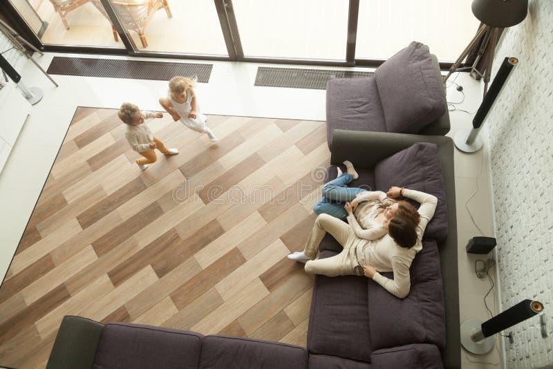 Kinder, welche die Eltern zu Hause sich entspannen auf Couch, Draufsicht spielen lizenzfreies stockbild