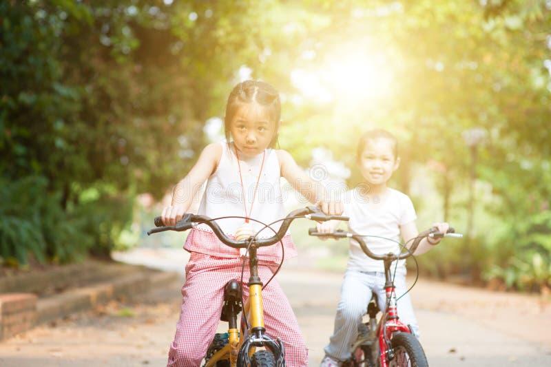 Kinder, welche die Fahrräder im Freien reiten stockfotos
