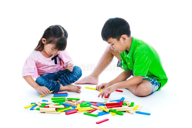 Kinder, welche die hölzernen Blöcke des Spielzeugs, lokalisiert auf weißem Hintergrund spielen stockfotos