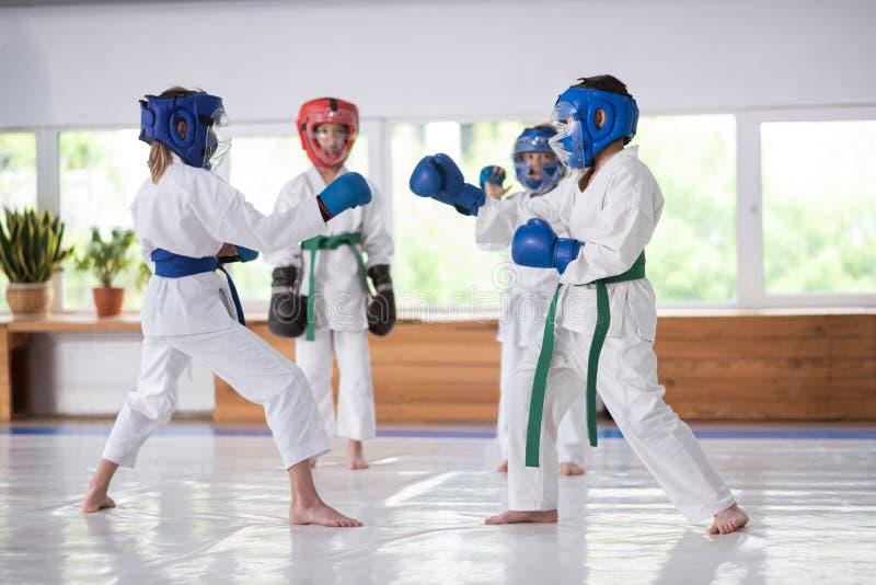 Kinder, welche die Kampfkünste tragen Sturzhelme während Verpacken studieren lizenzfreies stockbild