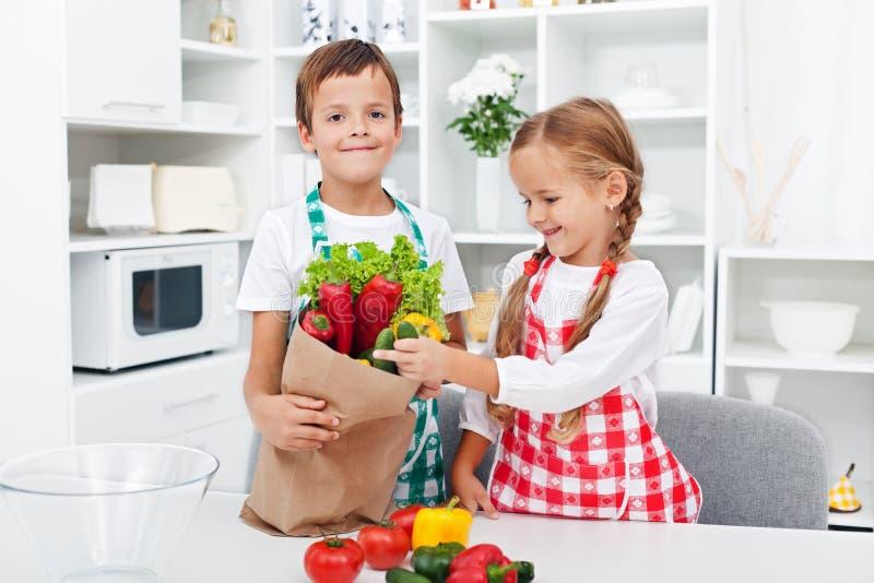 Kinder, welche die Lebensmittelgeschäfte entpacken lizenzfreies stockfoto