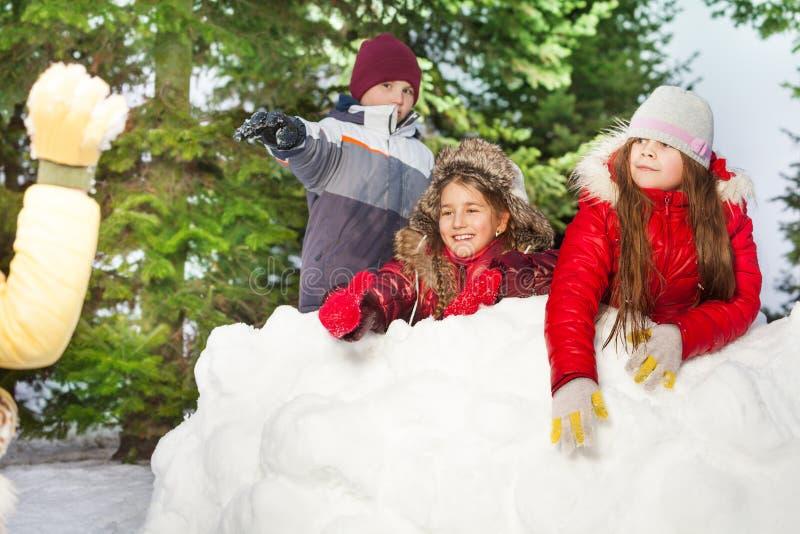 Kinder, welche die Schneebälle sich verstecken nach Schneeturm werfen stockfoto