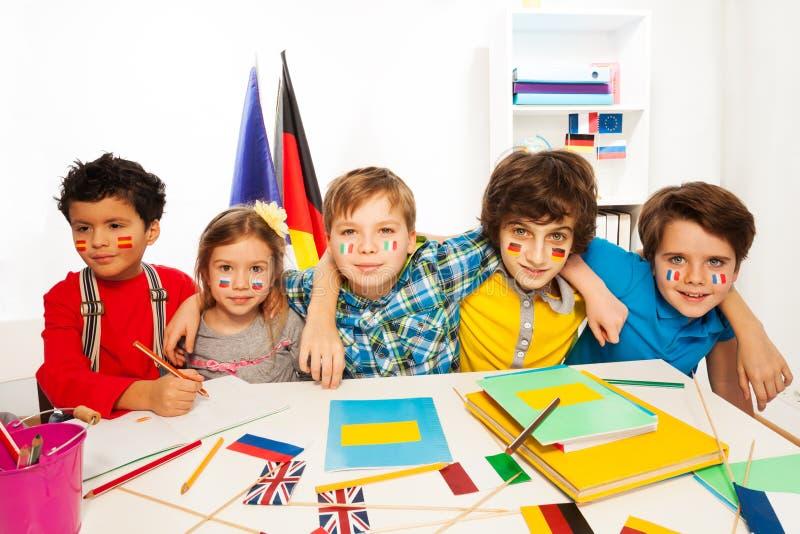 Kinder, welche die Sprachen sitzen in der Linie an einem Schreibtisch lernen stockfotos