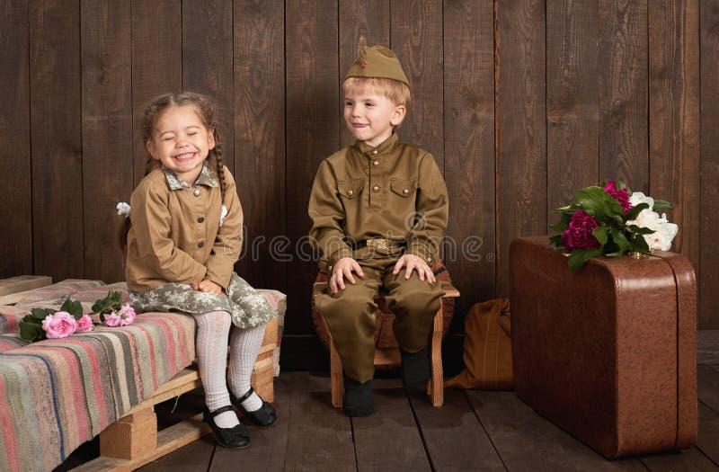 Kinder werden in den Retro- Militäruniformen gekleidet, die der Armee, dunkler hölzerner Hintergrund, Retrostil einen Soldaten sc stockfotografie