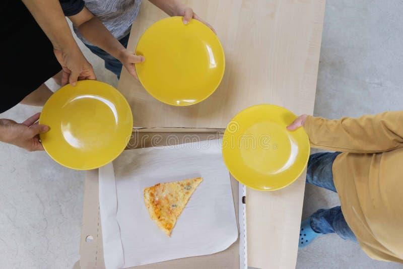 Kinder werden gebeten, ihnen das letzte St?ck von den K?sen der Pizza 4 zu geben, die im Kasten nach einem Familienabendessen ble stockfotografie