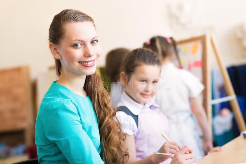 Kinderabgehobener betrag mit dem Lehrer lizenzfreies stockbild