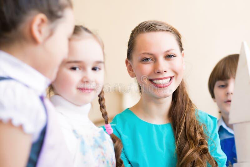 Kinderabgehobener betrag mit dem Lehrer lizenzfreie stockfotos