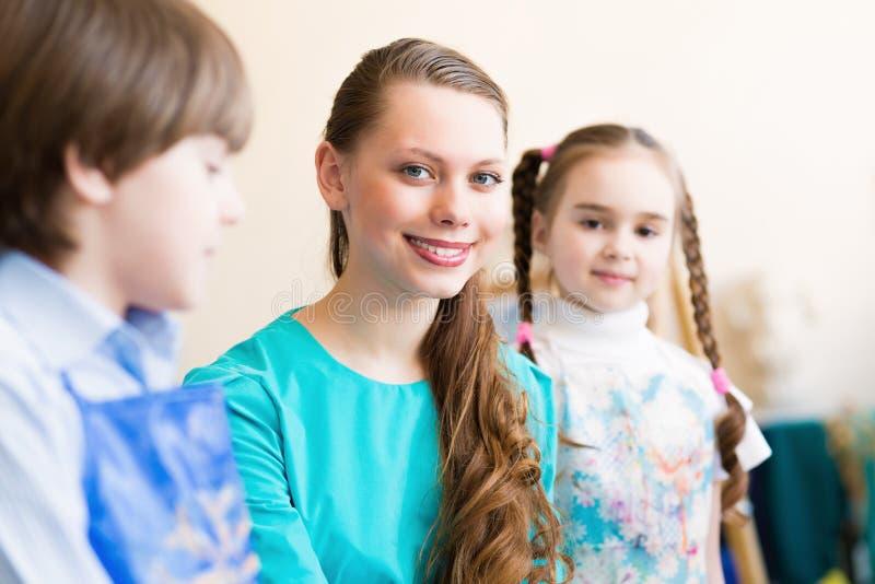 Kinderabgehobener betrag mit dem Lehrer stockbilder