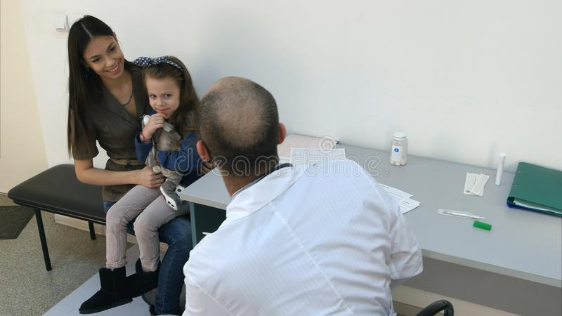 Kinderarztdoktor, der herauf Patienten des kleinen Mädchens mit Häschenspielzeug zujubelt lizenzfreies stockbild